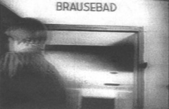 GI opens door of bogus 'gas chamber' at the Dachau; portion of a 1945 US propaganda film