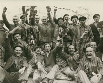 Joyful Dachau camp inmates cheer their American liberators, April 29, 1945