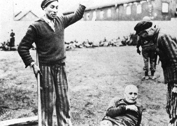 Newly liberated Dachau prisoners jeer a prostrate German prison guard