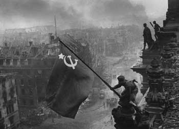 Soviet troops hoist the red hammer and sickle flag over the Reichstag in Berlin, May 1945